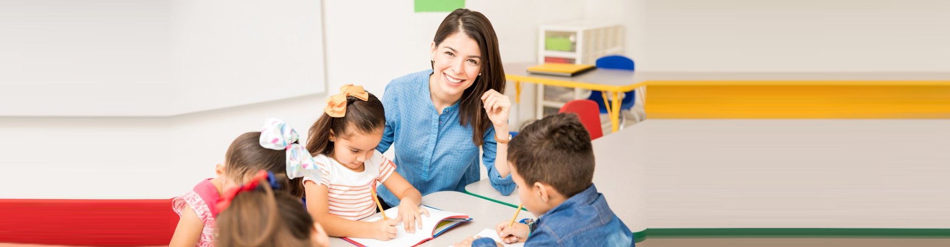 teacher helping the pre-school student